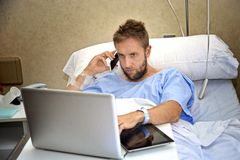 Workaholic business man in hospital room lying in bed sick and injured working with mobile phone computer laptop. Young workaholic business man in hospital room Royalty Free Stock Photography