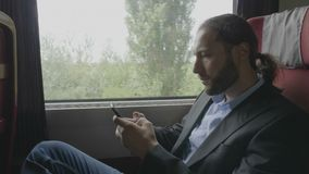 Workaholic business young bearded man on train commuting to work using smartphone texting and reading office emails -. Workaholic business young bearded man on stock footage