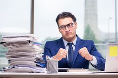 The workaholic businessman overworked with too much work in office stock photography