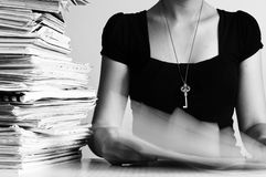 Workaholic with key to success. A workaholic surrounded by paper with the key to success around her neck stock photography