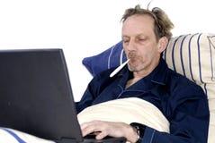 Workaholic, krank im Bett mit Laptop. Lizenzfreies Stockfoto