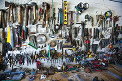 Workbench. Handtools organized on a pegboard in a home shop above a workbench Royalty Free Stock Photo