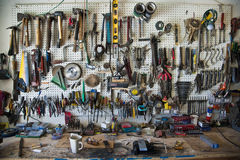 Workbench. Handtools organized on a pegboard in a home shop above a workbench Stock Photo