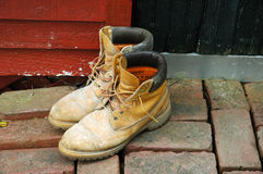 Workboots outside the door. Mud-caked workboots on the brick walkway outside the black door to a bright red shed stock image