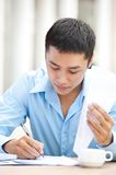 Workday. Young businessman sitting at the table and writing something in documents Royalty Free Stock Image