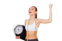 Worked off her excess weight. Happy young woman in sports clothing holding weight scale and gesturing while standing isolated on white Royalty Free Stock Photos