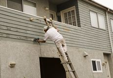Worker. Man on a ladder doing home repair with painting and sanding Royalty Free Stock Photos