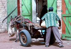 Worker. Mauritani men carry a sack to a wagon in Atar Mauritania Stock Photos