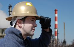 Worker. Male worker holding his safety helmet in industrial environment Royalty Free Stock Image