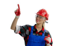 Worker. A female worker dressed in a shirt and overalls, hard hat and gloves, points upwards Stock Images