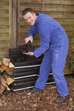 Worker. Man in workwear stacking coal briquet for burning stove (chimney Stock Photo