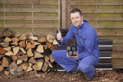 Worker. Man in workwear stacking coal briquet for burning stove (chimney Stock Photos