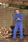 Worker. Man in workwear stacking coal briquet for burning stove (chimney Stock Images