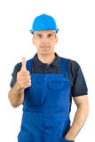 Worker. The worker in a blue overalls and a blue helmet shows the big finger Stock Photography