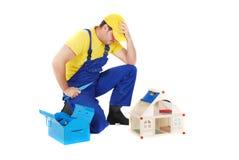 Worker. Repair the broken house Stock Images