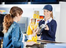 Worker Accepting Payment From Woman Through NFC. Smiling female worker accepting payment from women through NFC technology at cinema concession stand Stock Images
