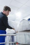 Worker adding malt in boiler. Side view of a bearded man pouring out malt from bag into boiler on a craft beer process stock images