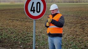 Worker with adjustable wrench near road sign stock video footage