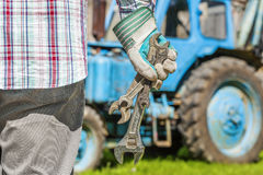 Worker with adjustable wrench near the tractor Stock Photo