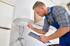Worker Adjusting Temperature Of Water Heater. Male Worker With Clipboard Adjusting Temperature Of Water Heater Royalty Free Stock Photo