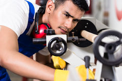 Worker adjusting turning machine in factory. Preparing the manufacturing process Stock Images