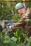 A worker adjusts the mechanism outdoors. In dense thickets of a grass and bushes Stock Photos