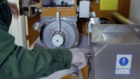 Worker adjust the paper tape inside the machine for making tea bags. Worker adjusts the paper tape inside the conveyor for making tea bags. Close-up. Prores stock footage