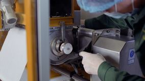 Worker adjust paper tape inside of machine for making tea bags, work at factory. Worker adjusts the paper tape inside the conveyor for making tea bags. Close-up stock video footage