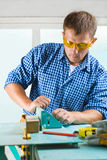 Worker adjusts the woodworking mashine Royalty Free Stock Photography