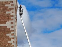 A worker, on the aerial platform of the cherry picker, maintains the facade of the building. Blue sky with fluffy clouds on backgr. Ound royalty free stock photos