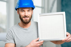 Worker with air filter. Worker holding air filter for installing in the house ventilation system. Purity of the air concept Stock Photos