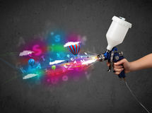 Worker with airbrush and colorful abstract clouds and balloons Royalty Free Stock Photo