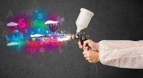 Worker with airbrush and colorful abstract clouds and balloons Stock Images