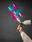 Worker with airbrush and colorful abstract clouds and balloons Stock Photo