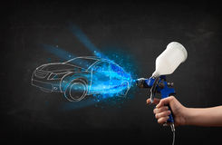 Worker with airbrush gun painting hand drawn car lines. Worker with airbrush gun painting hand drawn white car lines Stock Photo
