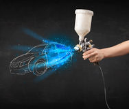 Worker with airbrush gun painting hand drawn car lines Royalty Free Stock Image