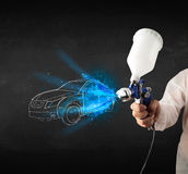Worker with airbrush gun painting hand drawn car lines Stock Photo
