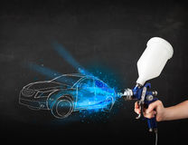 Worker with airbrush gun painting hand drawn car lines Royalty Free Stock Photography