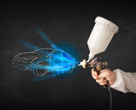 Worker with airbrush gun painting hand drawn car lines Royalty Free Stock Images