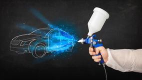 Worker with airbrush gun painting hand drawn car lines Stock Image