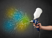 Worker with airbrush gun paints colorful lines and splashes Royalty Free Stock Images