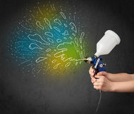 Worker with airbrush gun paints colorful lines and splashes Royalty Free Stock Photos