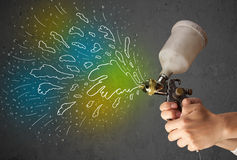 Worker with airbrush gun paints colorful lines and splashes Royalty Free Stock Photography