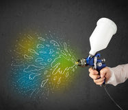 Worker with airbrush gun paints colorful lines and splashes Royalty Free Stock Image