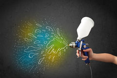 Worker with airbrush gun paints colorful lines and splashes Stock Photo