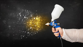 Worker with airbrush painting with glowing golden paint Royalty Free Stock Photos