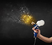 Worker with airbrush painting with glowing golden paint Royalty Free Stock Photography