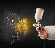 Worker with airbrush painting with glowing golden paint. And particles Stock Images