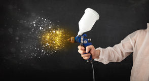 Worker with airbrush painting with glowing golden paint Stock Image