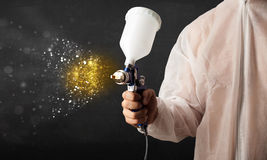 Worker with airbrush painting with glowing golden paint Royalty Free Stock Photo